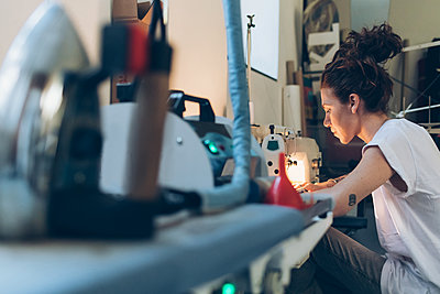 Fashion designer working at sewing machine - p429m2058361 by Eugenio Marongiu