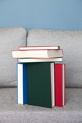 Stack of books on a sofa - p4540857 by Lubitz + Dorner
