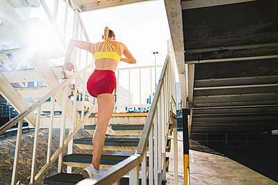 Young woman exercising in urban environment, running up stairs, rear view - p924m1187553 by Kevin Kozicki