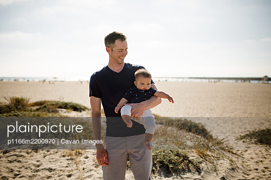 Father Smiling & Casually Holding Son on Beach - p1166m2200970 by Cavan Images