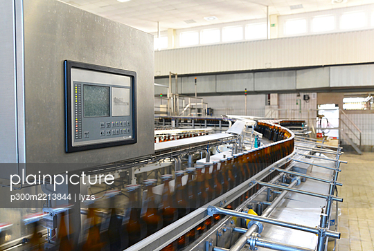 Germany, beer bottles on an assembly line of a bottling plant of a brewery - p300m2213844 by lyzs