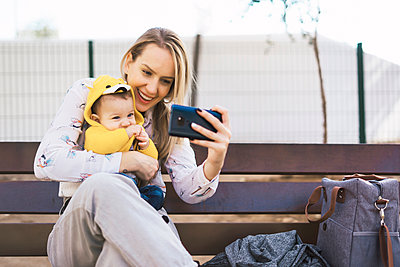 Happy mother resting with baby boy on a park bench taking a selfie - p300m2155956 by Eloisa Ramos