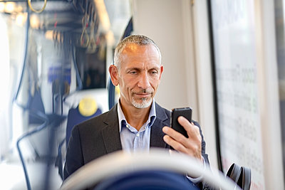 Male professional using smart phone while sitting in tram - p300m2287620 by Emma Innocenti
