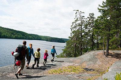 Family with four children walking along lakeshore - p575m696327f by Fredrik Schlyter