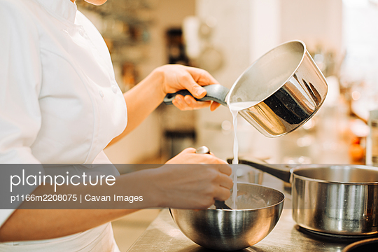 Female chef pouring milk in bowl while stirring - p1166m2208075 by Cavan Images