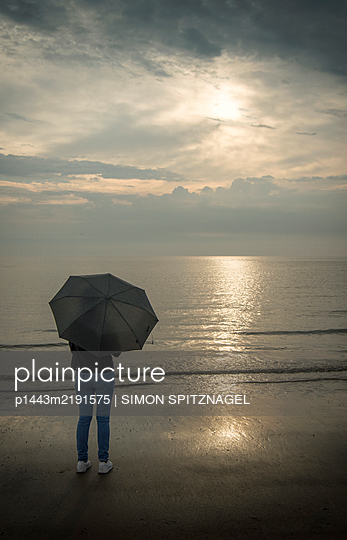 Woman with umbrella on the beach - p1443m2191575 by SIMON SPITZNAGEL