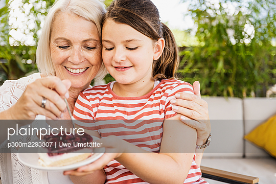Granddaughter and mother eating dessert while sitting at balcony - p300m2293807 by Uwe Umstätter