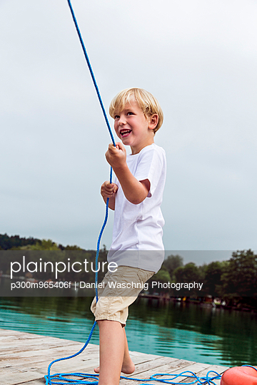 Portrait of smiling little boy standing on a jetty pulling a rope - p300m965406f by Daniel Waschnig Photography