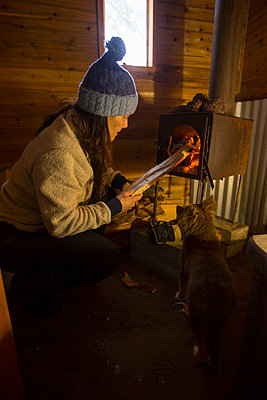 A woman building a fire in a rustic sauna. - p1166m2202317 by Woods Wheatcroft photography