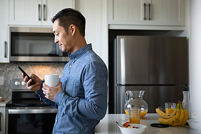 Man drinking coffee and using smart phone in morning kitchen - p1192m2088565 by Hero Images