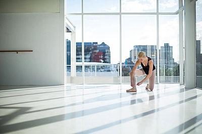 Ballerina tying her ballet shoes - p1315m1230730 by Wavebreak