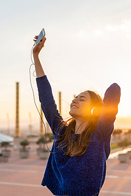 Spain, Barcelona, Montjuic, happy young woman listening to music with headphones at sunset - p300m2058637 by VITTA GALLERY