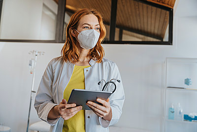 Female doctor with face mask standing with digital tablet at clinic - p300m2266928 by Mareen Fischinger
