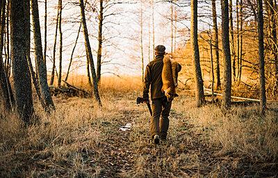 Hunter carrying fox - p312m1472790 by Hans Berggren