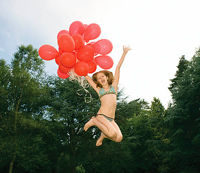 Girl with red balloons jumping in garden - p4293254f by Karan Kapoor