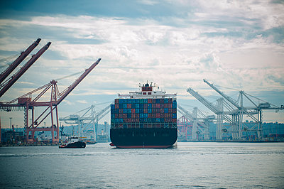 Tugboat and container ship in industrial harbor - p555m1414206 by Pete Saloutos