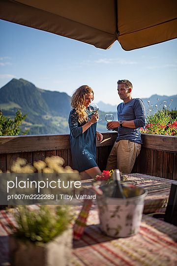 Young couple takes a glass of wine on the terrace - p1007m2222289 by Tilby Vattard