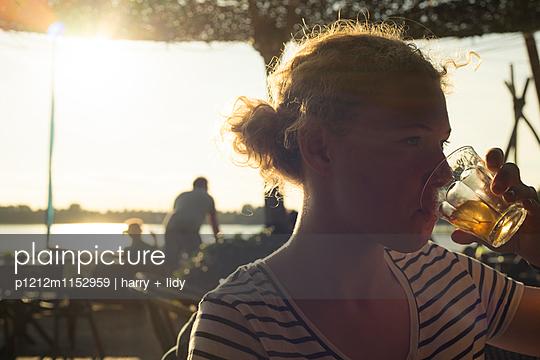 Strandbar - Mädchen trinkt eine Limo - p1212m1152959 von harry + lidy