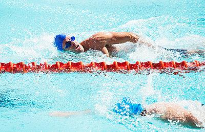 Swimmers racing in pool - p1023m923584f by Paul Bradbury