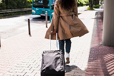 Young woman with luggage at bus stop - p300m1188652 by Uwe Umstätter