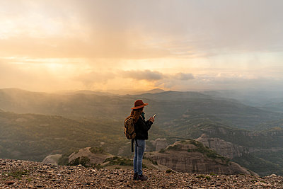 Woman with backback, standing on mountain, looking at view, using smartphone - p300m2078977 von VITTA GALLERY