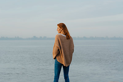 Germany, Hamburg, woman standing at the Elbe shore - p300m2080471 by Joseffson