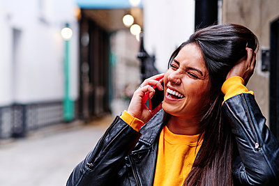 Cheerful young woman squinting while talking on mobile phone in city - p300m2273665 by Angel Santana Garcia
