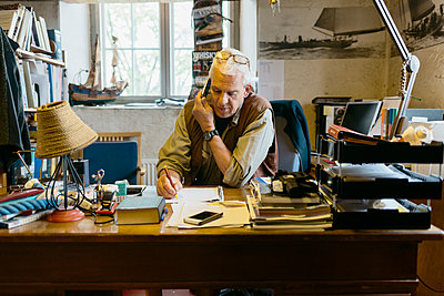 Rope maker talking on his cell phone at his desk in shop - p352m2041256 by Folio Images