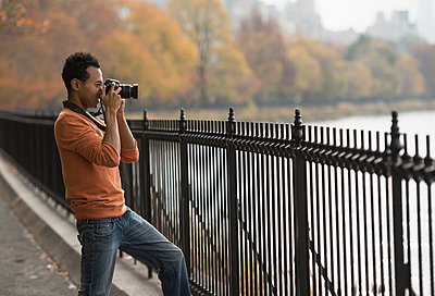 Mixed race man taking photograph on waterfront - p555m1414389 by JGI/Tom Grill
