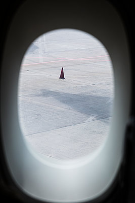 Traffic cone on runway seen through window - p628m1476248 by Franco Cozzo