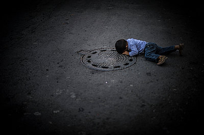 Boy looking into a manhole - p1007m1134838 by Tilby Vattard