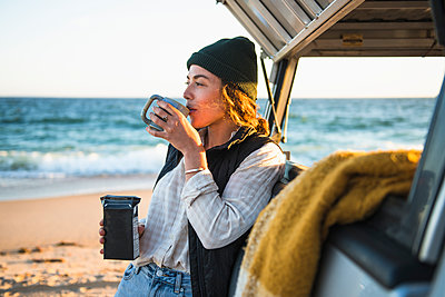 Young woman enjoying drink in mug while beach car camping alone - p1166m2285576 by Cavan Images