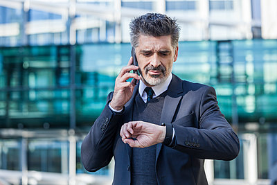 Businessman outdoors on cell phone checking the time - p300m1205603 by Tom Chance