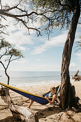 Young woman reading book while resting in hammock at beach, Maui, Hawaii, USA - p300m2199205 by letizia haessig photography