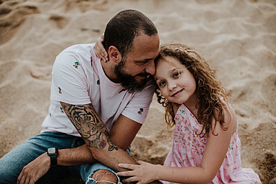 Smiling daughter sitting with father on sand at beach - p300m2202662 by Gala Martínez López
