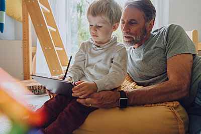Father looking son using digital tablet computer in bedroom - p300m2266688 by Mareen Fischinger