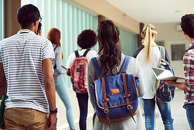 Students walking in school corridor, rear view - p623m1579544 by Frederic Cirou