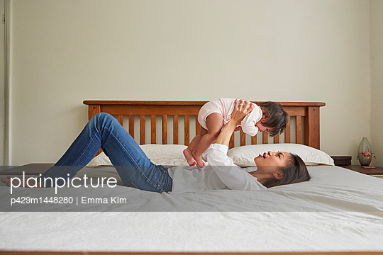 Woman lying on bed holding up baby daughter - p429m1448280 by Emma Kim