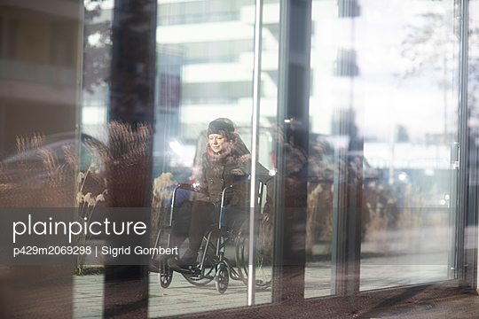 Reflection of woman in wheelchair on glass windows of building - p429m2069298 by Sigrid Gombert