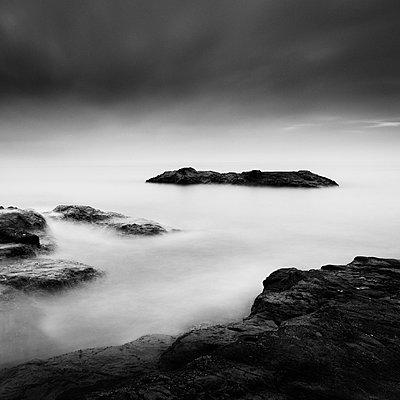 Long exposure shot of dark clouds over sea stacks in Enoshima - p1166m2246698 by Cavan Images