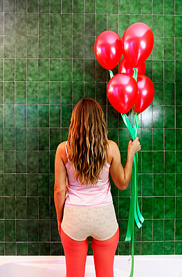 Woman holding balloons in a bathroom - p1521m2126576 by Charlotte Zobel