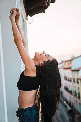 Beautiful young woman stretching on balcony above the city at sunset - p300m2042333 von Kike Arnaiz