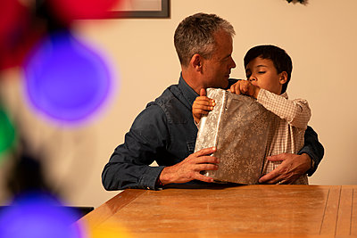 Father with curious son unwrapping Christmas present on table at home - p300m2243993 by Pete Muller