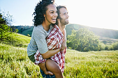 Smiling Man carrying girlfriend piggyback on hill - p555m1303373 by Peathegee Inc