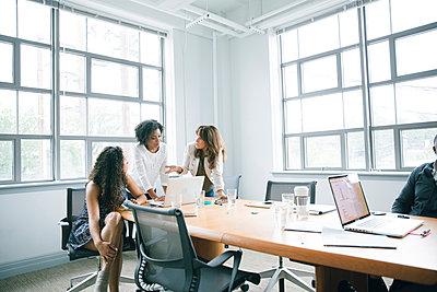 Businesswomen using laptop in meeting - p555m1504112 by John Fedele