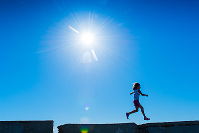 France, Girl jumping on old bunker ruins - p829m2296809 by Régis Domergue