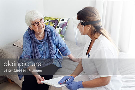 Nurse with elderly woman at home - p312m2299644 by Plattform