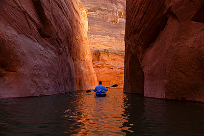 Rear view of hiker kayaking on Lake Powell amidst canyons - p1166m1509620 by Cavan Images