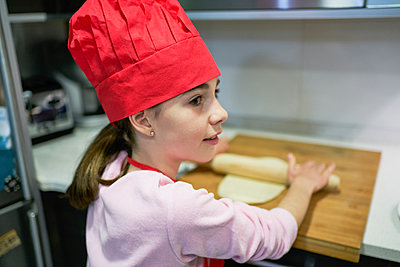 Girl with red chef's hat makes pizza dough with a rolling pin - p1166m2201418 by Cavan Images