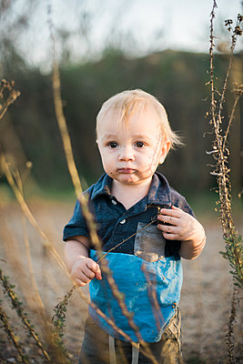 Little toddler boy playing with dried flowers - p1166m2201446 by Cavan Images